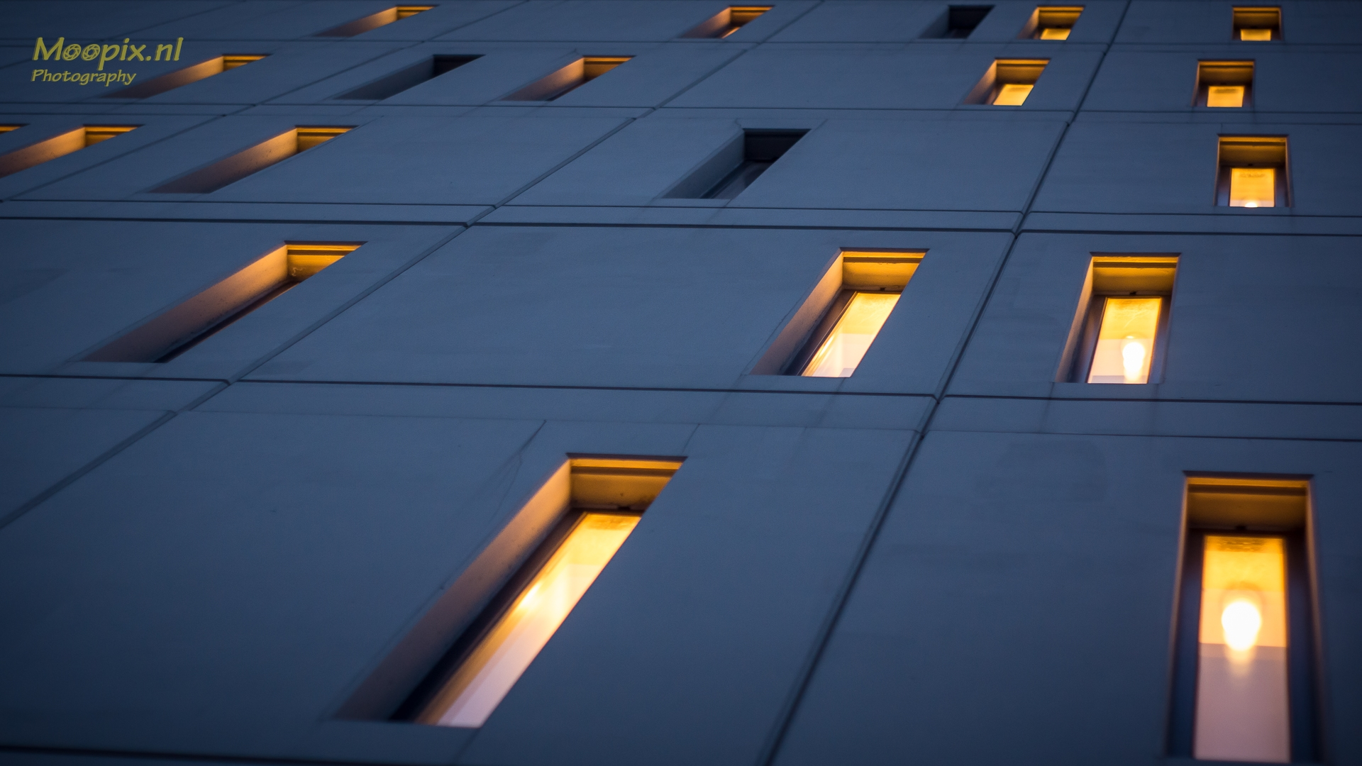 Architectuur : steile muur met verlichte ramen in willekeurig patroon
