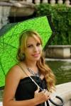 Meisje met groene parasol zittend bij fontein