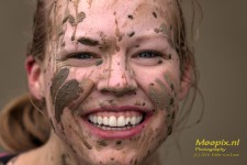 Obstacle run girl with muddy face and big smile