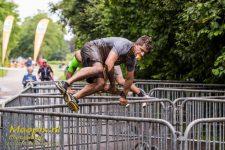 Foto van een obstacle runner die een hindernis neemt met een broodje in zijn mond
