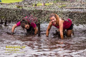 2 meisjes tijgerend door de modder bij een Obstacle Run